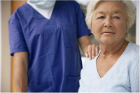 Elder female patient with health care provider's hand on shoulder.