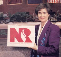 Former NINR Director Dr. Ada Sue Hinshaw holding NINR's plaque for Institute status at NIH.