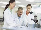 Two female and one male researcher in lab coats working by a microscope