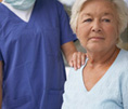 Senior woman in hospital gown with health care provider's hand on shoulder.