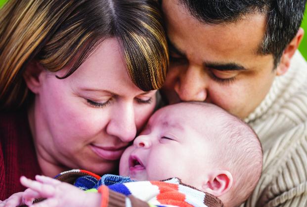 pareja besándose bebé
