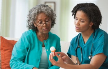 home nurse explaining medication to woman