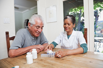 home nurse helping man with medication