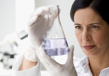 Female researcher examines beaker with fluid